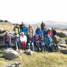 Group of walkers sat on Dartmoor tor